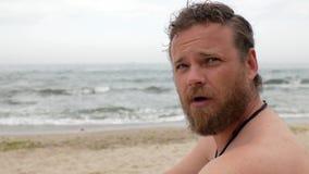 Un tipo con una barba sui precedenti del mare sta pettinando la sua barba con un pettine di legno un video di 4 K archivi video