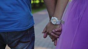 Un tipo con una ragazza che cammina nel tenersi per mano del parco I giovani amanti camminano Primo piano delle loro mani Isolato archivi video