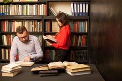 Un tipo con una ragazza che si prepara per l'esame ha letto i libri nella biblioteca Fotografia Stock