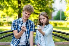 Un tipo con una ragazza di estate nel parco su un banco Il gesto delle mani mostra una figura Il concetto di sfiducia Immagine Stock