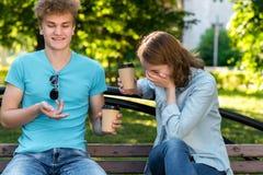 Un tipo con una ragazza di estate in un parco in natura Dice uno scherzo divertente Le risate della ragazza con lei la consegnano Fotografie Stock Libere da Diritti