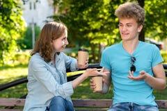 Un tipo con una ragazza felice in un parco sulla natura di estate si siedono sul banco Tiene le tazze con caffè o tè in sue mani Immagine Stock Libera da Diritti