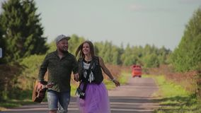 Un tipo di due amanti e una ragazza sono su una strada campestre La tenuta del tipo una chitarra Si divertono e comunicano stock footage
