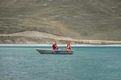 Un tipo e una ragazza in un giubbotto di salvataggio su una barca Fotografia Stock Libera da Diritti