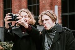 Un tipo e una ragazza prendere le immagini se stessi e fare i fronti divertenti fotografia stock libera da diritti