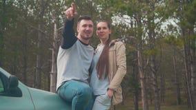 Un tipo e una ragazza sono stare, appoggiantesi un'automobile nella foresta che il tipo mostra alla ragazza qualcosa nella distan video d archivio