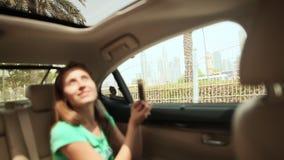 Un tipo e una ragazza viaggiano nel Dubai in macchina ed ammirano la città video d archivio