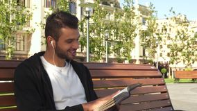 Un tipo felice sta leggendo un libro in un vicolo della città video d archivio