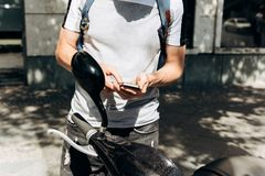 Un tipo o un turista attiva o affitta un motorino elettrico facendo uso di un'applicazione mobile su un telefono cellulare immagine stock