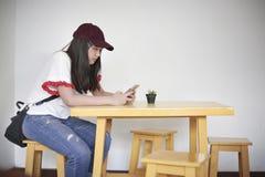 Un tipo que se sienta mensajes del adolescente en los teléfonos móviles Foto de archivo
