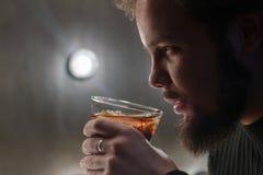 Un tipo serio con una barba tiene un vetro di cola o di whiskey con ghiaccio in sua mano Controlli la modellistica della luce per immagine stock libera da diritti