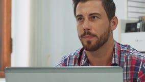 Un tipo serio del individuo algo en el teclado en el ordenador metrajes