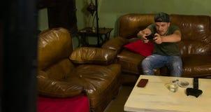 Un tipo sta giocando molto intensivelly un video gioco fotografia stock libera da diritti