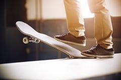 Un tipo sta su una rampa su un pattino e fa un calo nel trucco fotografia stock