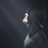 Un tipo in un abito nero che sta nello scuro immagini stock libere da diritti