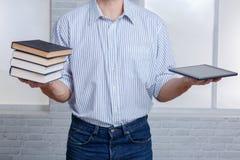 Un tipo in una mano che tiene una pila di libri e di compressa Immagine Stock