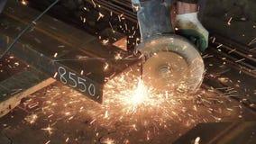 Un tir étroit sur la scie électrique pour le métal, le constructeur dans les gants protecteurs coupe les faisceaux en métal, les  clips vidéos