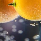 Un tir en gros plan d'agrume dans un verre de l'eau avec un bon nombre de beau fond de bulles pour des cartes de voeux et le mate Photographie stock libre de droits