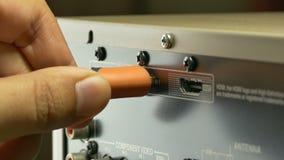 Un tir en gros plan d'un ouvrier brancher-dans un câble de HDMI au dos de banque de vidéos