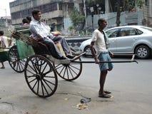 Un tirador del carrito de la mano tira de un hombre en el medio del camino Imagen de archivo libre de regalías
