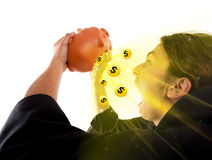 Un tirante che trova il tesoro conia in una banca piggy Immagine Stock