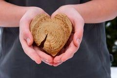 Un tirante con un cuore in sue mani Fotografie Stock Libere da Diritti
