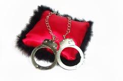 Un tiro aislado de un par de legcuffs de la calidad en la almohada Fotos de archivo libres de regalías