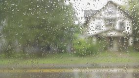Un tiro ascendente cercano de las gotas de agua que ruedan abajo una ventana desde adentro durante un día lluvioso 4K UHD Timela almacen de video