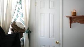 Un tiro bloqueado del plumón de un trastero a puerta cerrada del armario en el dormitorio blanco metrajes