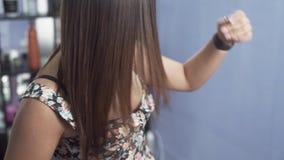 Un tiro a cámara lenta del primer de una muchacha en un salón de belleza admira su pelo brillante recto largo después de endereza almacen de video