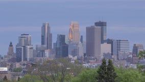 Un tiro crepuscular del horizonte de Minneapolis que sube sobre una hilera de árboles verde almacen de video