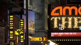 Un tiro de iluminado firma adentro Times Square en la noche almacen de metraje de vídeo