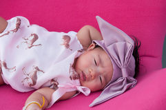 Un tiro de un bebé lindo con la venda púrpura mientras que el dormir y el jugar en la silla rosada/se centran en la niña pequeña Imagen de archivo libre de regalías