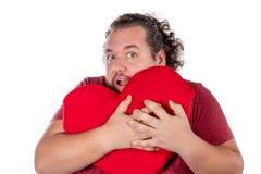 Un tiro del estudio de un hombre gordo que sostiene una almohada en forma de corazón roja aislada en el fondo blanco imágenes de archivo libres de regalías