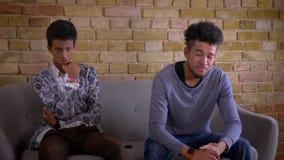 Un tiro del primo piano di due giovani amici maschii che guardano dramma triste sulla TV che si siede insieme sullo strato all'in stock footage