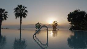 Un tiro del steadicam de una piscina vacía abierta por la puesta del sol almacen de video