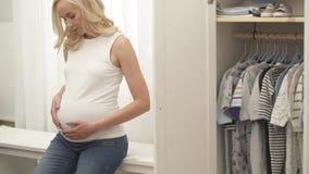 Un tiro del vientre embarazada de los woman's acariciado por sus manos la cámara se levanta Un rubio bonito está mirando abajo metrajes