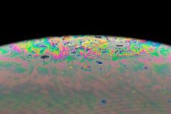 Un tiro macro de una burbuja de jab?n con una estructura hermosa y colorida - fondo negro fotos de archivo