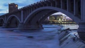 Un tiro medio de los puentes de Minneapolis que cruzan el río Misisipi poderoso en el St Anthony Power Park Falls en el crepúscul metrajes