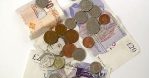 Un tiro que mira abajo en las monedas y los billetes de libra que giran almacen de metraje de vídeo