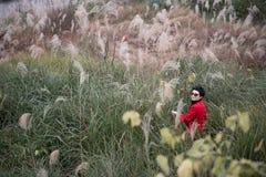 Un tiroteo chino de la muchacha en el fondo de Miscanthus Fotografía de archivo libre de regalías