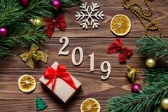 Un titolo di 2019 nuovi anni sulla tavola di legno lussuosa circondata con regalo di Natale, le fette di limone, le campane ed al Fotografie Stock