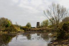 Un tocón viejo del molino de viento reflejó en el agua inmóvil del lago en las minas del siglo XIX abandonadas de la ventaja en C Foto de archivo libre de regalías
