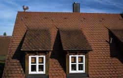 Un toit rouge avec de petites fenêtres blanches Images stock
