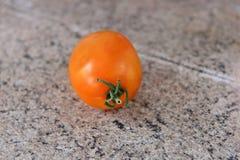 Un tomate anaranjado en un fondo de madera fotos de archivo