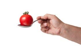 Un tomate en una cuchara Foto de archivo