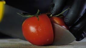 Un tomate grande miente en un tablero de madera en un fondo aislado negro, el cocinero corta un tomate en dos pedazos almacen de video