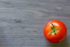 Un tomate maduro en un fondo azul Imagenes de archivo