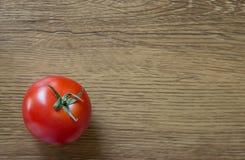 Un tomate maduro en un fondo de madera Imagen de archivo