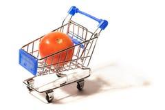 Un tomate rojo grande en un pequeño carro de la compra Imagen de archivo libre de regalías